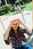 Child in pink cap swinging on Playground - heart shape stock photography