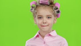 Child in pink curlers looks in the mirror and paints with red lipstick lips. Green screen. Close up. Slow motion stock footage
