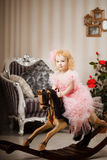 Child in a pink dress on a toy horse Royalty Free Stock Images
