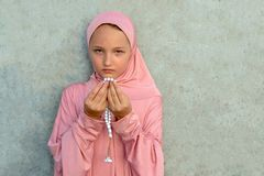 A child in a pink hijab with a beads in his hands with copy space. People religious lifestyle concept stock photography