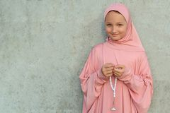 A child in a pink hijab with a beads in his hands with copy space. People religious lifestyle concept royalty free stock photos