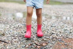 Child in a pink rubber boots in the rain jumping in puddles. Kid playing in summer park. Outdoor fun by any weather royalty free stock image
