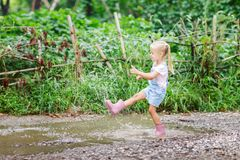 Child in a pink rubber boots in the rain jumping in puddles. Kid playing in summer park. Outdoor fun by any weather stock photography