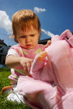 Child with pink rucksack. Young girl child outdoor sitting on the grass and look for her doll toy from her rucksack Stock Photos