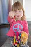 Child pink shirt sitting on floor complaining. Portrait of blonde three years old child with pink shirt blue peace hippie symbol, sitting on floor kitchen Royalty Free Stock Photo