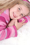 Child in pink sweater on white fur Stock Image