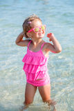 Child in pink swimsuit and sunglasses at the sea. Happy, smiling. Summer vacation. Enjoy sun. Royalty Free Stock Photography