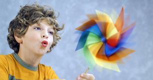 Child and a pinwheel. Blonde child blowing a pinwheel Stock Photo