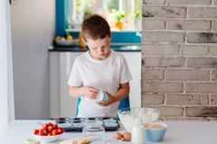Child placing cupcake forms in baking tray Stock Photos