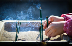A child placing incense at a temple in Japan Stock Photo