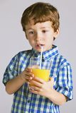 Child with plaid shirt drinking a fresh orange juice. Stock Photo