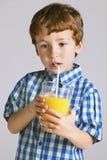 Child with plaid shirt drinking a fresh orange juice. Stock Photo