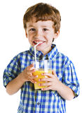 Child with plaid shirt drinking a fresh orange juice. Royalty Free Stock Images