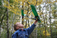 Child with plane. In autumn wood Stock Photo