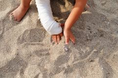 Child with plaster on his hand playing in the sand on the beach by the sea. royalty free stock photography