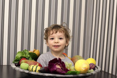 Child and plate of fruits Royalty Free Stock Images