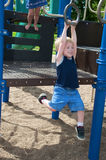 Child play. Young child having fun and playing in the park on a sunny day Stock Photography