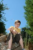 Child at Play. A young boy (12) looking forward throwing a small stick towards the camera whlist sitting on a rock. Greenery and clear blue sky to background Royalty Free Stock Image