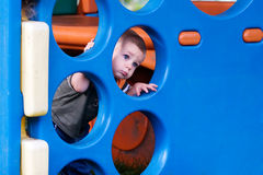 Child in play area. Young boy looking through play equipment in play area Royalty Free Stock Photo