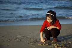 Child play on the beach. In autumn Stock Images