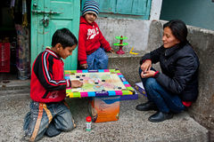 Child play. A Bhutia woman is playing carrom in off time with her two children in front of her shop at Gangtok, Sikkim Stock Image