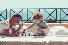 Child play chess with father. Summer vacation of happy family. Family travel with kid on fathers day. father with son on. Balcony play chess. Love and trust as royalty free stock images