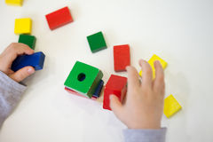 Child play with colored wooden brick shapes Stock Images