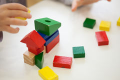 Child play with colored wooden brick shapes Royalty Free Stock Photography