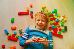 Child play with colorful plastic blocks indoor. Cute child playing with colorful plastic blocks indoor royalty free stock photo