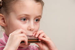 Child play harmonica. Young girl play blues harmonica Stock Images