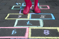 Child is play hopscotch. Young girl is playing hopscotch Royalty Free Stock Photography