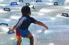 Child play with Inflatable clear inner tubes Royalty Free Stock Image