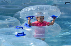 Child play with Inflatable clear inner tubes Royalty Free Stock Photography