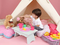 Child Play: Pretend Food, Toys and Teepee Tent. Toddler child, kid, engaged in pretend play with food, stuffed toys, and teepee tent royalty free stock photography