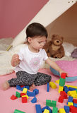 Child Play: Pretend Games Toys and Teepee Tent. Toddler child, kid, engaged in pretend play with stuffed toys, and teepee tent stock photo