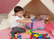 Child Play: Pretend Play with Blocks and Teepee Tent. Toddler child, kid, engaged in pretend play with building blocks, toys, and teepee tent royalty free stock image