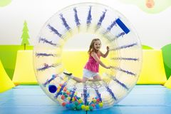 Child play in roller wheel. Kids on trampoline. Child in roller wheel jumping on colorful playground trampoline. Kids jump in inflatable bounce castle on stock photos