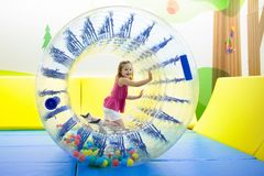 Child play in roller wheel. Kids on trampoline. Child in roller wheel jumping on colorful playground trampoline. Kids jump in inflatable bounce castle on stock images