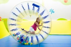 Child play in roller wheel. Kids on trampoline. Child in roller wheel jumping on colorful playground trampoline. Kids jump in inflatable bounce castle on royalty free stock images