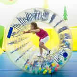 Child play in roller wheel. Kids on trampoline. Child in roller wheel jumping on colorful playground trampoline. Kids jump in inflatable bounce castle on stock photography