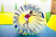 Child play in roller wheel. Kids on trampoline. Child in roller wheel jumping on colorful playground trampoline. Kids jump in inflatable bounce castle on stock photo