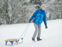 Child play in snow with sled. Happy boy riding sled and having fun. Child play outdoors in snow - sledding. Kid sled in snowy park in winter. Outdoor fun for Royalty Free Stock Photography