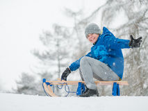 Child play in snow with sled Stock Images