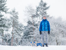 Child play in snow with sled. Happy boy riding sled and having fun. Child play outdoors in snow - sledding. Kid sled in snowy park in winter. Outdoor fun for Stock Photos