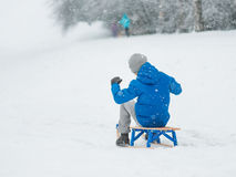 Child play in snow with sled. Happy boy riding sled and having fun. Child play outdoors in snow - sledding. Kid sled in snowy park in winter. Outdoor fun for Stock Photography