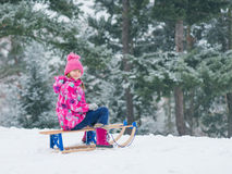 Child play in snow with sled Royalty Free Stock Images