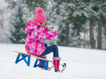Child play in snow with sled Royalty Free Stock Photography