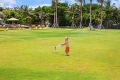 Child play, swim and splash under water sprinkler spray royalty free stock photos