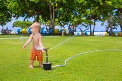 Child play, swim and splash under water sprinkler spray Stock Photos