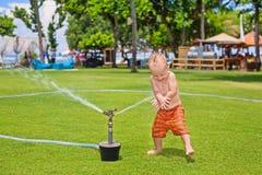 Child play, swim and splash under water sprinkler spray Stock Image